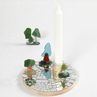 Un candeliere su piedistallo di legno con mosaici