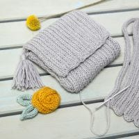 Una borsetta fatta da un tubolare a maglia decorato con una nappa