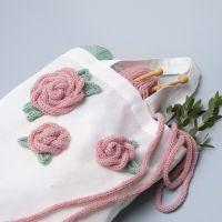Una shopping bag decorata con rose tubolari lavorate a maglia