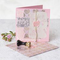 Un biglietto di auguri decorato con carta fatta a mano, disegni stampati, cera e sigillo