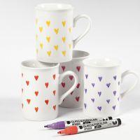 Tazze in porcellana decorate con cuori usando pennarelli per vetro e porcellana