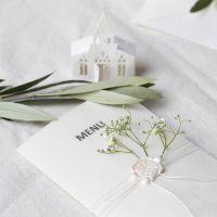 Un menu nei toni del bianco sporco con una chiesetta fustellata e carta velina