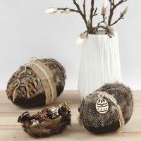Un uovo in cartapesta in due parti decorato con piume naturali e spago