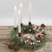 Una corona dell'Avvento decorata con materiali naturali e candele LED