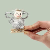 An angel made from a pom-pom and  pipe cleaners on a wooden peg
