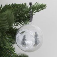 A Christmas bauble with a hole at the front decorated with artificial snow and mini figures