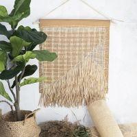 Una decorazione da appendere alla parete con carta in finta pelle, rattan e filati di carta rafia