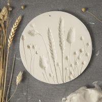 Un piatto di argilla autoindurente con impronte di fiori secchi