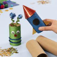Un razzo spaziale e un alieno da tubi di cartone decorati con materiali artigianali