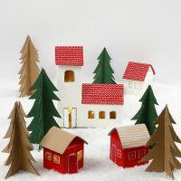 Un villaggio di Natale fatto di cartoni di latte/succhi e alberi di Natale di cartone riciclato